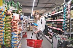 Het portret is een modieus meisje dat spaanders in supermakret kiest De meisjeskoper koopt bij een supermarkt stock afbeelding