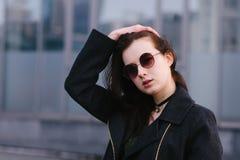 Het portret kleedde vrouwen stylishly mooi brunette in glazen, dat tegen een achtergrond van donkere stadsachtergrond stelt Stock Afbeeldingen