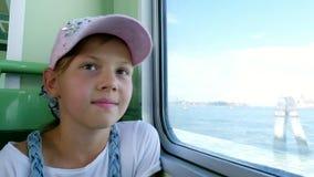 Het portret, mooi meisjeskind, in een roze GLB, kijkt uit het venster van het schip, bewondert het zeegezicht stock footage