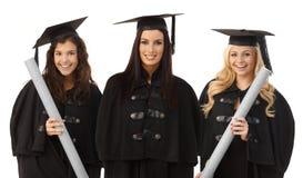 Portret van drie het vrouwelijke gediplomeerden gelukkig glimlachen royalty-vrije stock foto's
