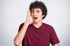 Het portret van aantrekkelijke krullende Europese kerel houdt handen de dichtbijgelegen wijd geopende mond, iets, wil somebody ho stock fotografie