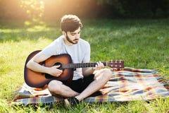 Het portret van aantrekkelijke modieuze gebaarde kerel met gitaarzitting kruiste benen op groen gras, het spelen muzikaal instrum stock fotografie