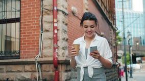 Het portret van aantrekkelijke smartphone van de meisjesholding en neemt koffie het lopen stock video