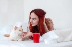 Het portret van het aantrekkelijke, tevreden, jonge, sexy roodharige vrouw ontspannen liggen in bed geniet van haar koffie in een stock foto's