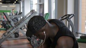 Het portret van Afro-Amerikaanse sportman die in de gymnastiek tijdens de onderbreking zit en de muziek luistert stock footage