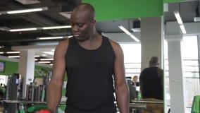 Het portret van Afro-Amerikaanse sportman die domoorvoorzijde doet heft in de moderne luxegymnastiek op stock footage
