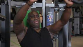 Het portret van Afro-Amerikaanse sportman die op de geneigde bank en de rijen op de machine zit stock videobeelden