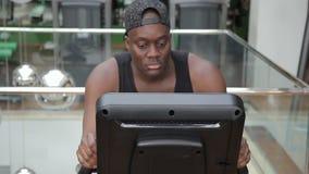 Het portret van Afro-Amerikaanse spotrsman het cirkelen stationaire bycicle in de moderne gymnastiek stock videobeelden