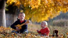 Het portret van het amuseren van kind zingt bij gitaar aan babybroer in de herfstpark stock video