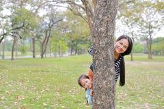 Het portret van Aziatische moeder en weinig kindmeisje verbergen lichaam achter boomboomstam in de zomertuin openlucht royalty-vrije stock afbeelding