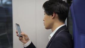 Het portret van het Aziatische zakenman typen messeges terwijl het reizen door trein stock video