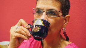 Het portret van bejaarde drinkt een kop thee op rode achtergrond stock footage
