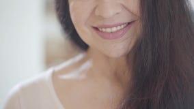 Het portret van het besnoeiingsgezicht van hogere vrouw met het glimlachen van lippen en schitterend lang donker haar die prettig stock videobeelden
