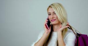 Het portret van besprekingen van een de jonge opgewekte blondevrouw op cel telefoneert en houdt kleurrijke het winkelen pakketten stock footage