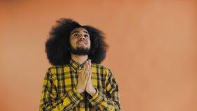 Het portret van het bidden Afrikaanse Amerikaanse kerel die vingers houden te kruisen en god gelieve op Oranje achtergrond gillen stock footage