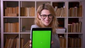 Het portret van blondeleraar op middelbare leeftijd toont het vreugdevol groene chromascherm van tablet in camera bij de biblioth stock videobeelden