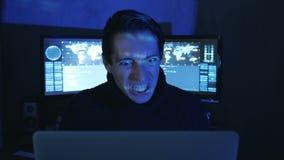 Het portret van Boze Hakkerprogrammeur gilt en toont agressie terwijl het werken bij de computer Spanning in de werkplaats stock video