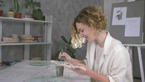 Het portret van ceramist kunstenaarsvrouw schildert kleiplaten met borstel en groene verf bij het bewerken van studio stock video
