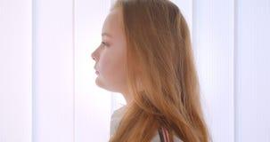 Het portret van het close-up zijaanzicht van jong vrij Kaukasisch meisje die camera binnen in de witte ruimte bekijken stock video