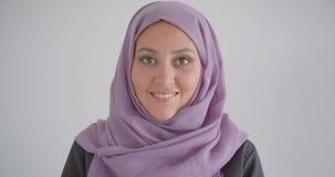 Het portret van het close-up zijaanzicht van jonge vrij moslimvrouw die in hijab camera bekijken die cheerfully met achtergrond g stock videobeelden