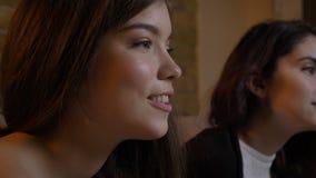 Het portret van het close-up zijaanzicht van twee jonge mooie vrouwen die op TV letten binnen lachend gelukkig in een comfortabel stock foto's