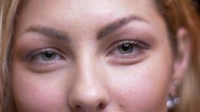 Het portret van het close-up zijaanzicht van volwassen aantrekkelijk blonde Kaukasisch wijfje die aan camera draaien die recht ca stock video