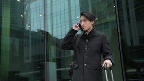 Het portret van de Aziatische mens, die zich dichtbij de moderne luchthaven en de vraag op zijn smartphone bevindt stock footage