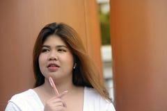 Het portret van de Aziatische mooie vette vrouw van het smileygezicht stelt en denkend Stock Fotografie