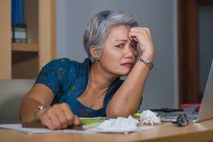 Het portret van de bureaulevensstijl van droevige en gedeprimeerde rijpe aantrekkelijke Aziatische vrouw die aan laptop beklemtoo stock foto