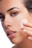 Vrouw die gezichts reinigend stootkussen gebruiken Stock Fotografie