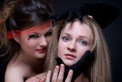 Het portret van de close-up van twee meisjes: goed & kwaad Royalty-vrije Stock Afbeeldingen