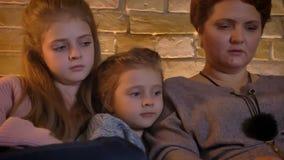 Het portret van de close-upfamilie van Kaukasische moeder en twee dochters die in tablet met vermaak in comfortabel huis letten o stock video