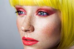 Het portret van de close-upschoonheid van kalm leuk jong vrouwelijk model met sproeten, rode make-up en gele pruik, die vooruit m royalty-vrije stock foto