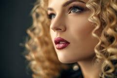 Het portret van de close-upschoonheid van het sexy gekrulde meisje van het haarblonde in studio met donkere achtergrond stock foto's