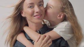 Het portret van de close-upstudio van moeder met haar dochteromhelzingen haar en gekust haar stock footage