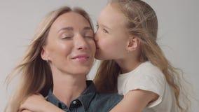 Het portret van de close-upstudio van moeder met haar dochteromhelzingen haar en gekust haar stock videobeelden