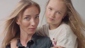 Het portret van de close-upstudio van moeder met haar dochteromhelzingen haar en gekust haar stock video