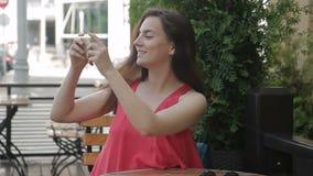 Het portret van de dame, die in openluchtkoffie zitten, verwijdert de zonnebril en neemt foto stock videobeelden
