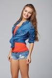 Het portret van de denimstijl van tienermeisje, over grijze achtergrond Royalty-vrije Stock Foto's