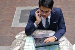 Het portret van de ernstige jonge bedrijfsmens spreekt op de telefoon voor zijn werk in het openluchtpark Royalty-vrije Stock Foto