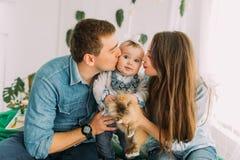 Het portret van de familie De ouders kussen de baby in de wang en houden het mooie konijn royalty-vrije stock afbeeldingen