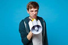 Het portret van de geïrriteerde jonge die mens in vrijetijdskleding houdt, gillend op megafoon op blauwe achtergrond in studio wo stock foto's