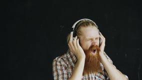 Het portret van de gebaarde jonge mens zet op hoofdtelefoons en het dansen terwijl aan muziek op zwarte achtergrond luister stock afbeeldingen
