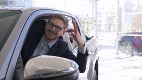 Het portret van de gelukkige zitting van de kerelcliënt in auto en toont sleutels van gekochte auto in toonzaal stock video