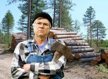 Het portret van de houthakker tegen een stapel logboeken Royalty-vrije Stock Afbeeldingen