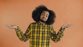 Het portret van de hulpeloze Afrikaanse Amerikaanse handen werpen opzij en mens die kent of schuint geen hulp op Oranje achtergro stock video