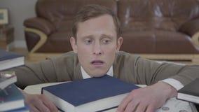 Het portret van de jonge bescheiden geklede mens die uit van achter het bureau in het bureau gluren, vele boeken is op de lijst E stock video