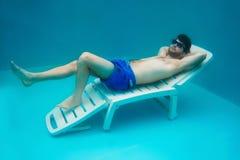 Het portret van de jonge man die op leggen sunbed onderwater Stock Afbeelding