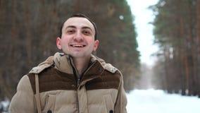 Het portret van de jonge mens in jasje lacht met gelukkig gezicht Mensentribunes in de winterbos stock video
