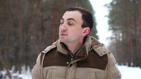 Het portret van de jonge mens in jasje ziet opzij eruit Mensentribunes in de winterbos stock videobeelden
